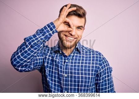 Young handsome blond man with beard and blue eyes wearing casual shirt standing doing ok gesture with hand smiling, eye looking through fingers with happy face.