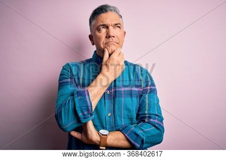Middle age handsome grey-haired man wearing casual shirt over isolated pink background with hand on chin thinking about question, pensive expression. Smiling with thoughtful face. Doubt concept.