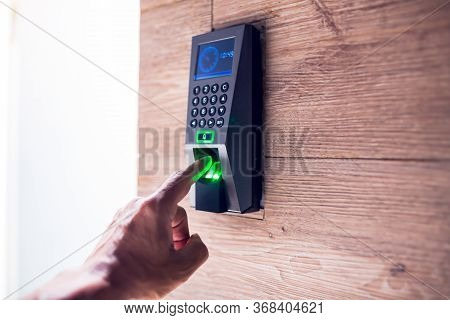Man Push Finger Down On The Electronic Control Machine To Access The Door.