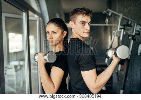 Young Athletic Fitness Trainers.active Couple Training Together.dumbbell Workout.fit Woman And Man S