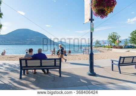 Penticton, British Columbia/canada - June 22, 2019: People Sit On Benches, Walk Along Lakeshore Driv
