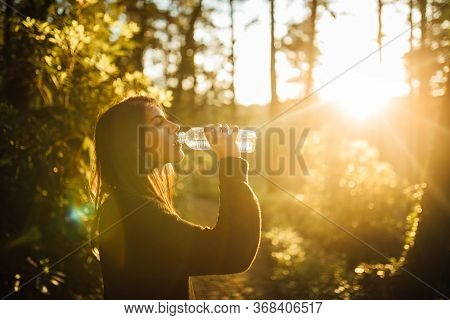 Young Woman Drinking Water From Bottle In Nature.bottled Water.hydration.water Intake For Healthy Bo