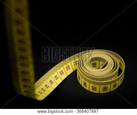 Yellow Measuring Tape With Scale In Centimeters. Yellow Measuring Tape Isolated On Black Background.
