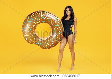 Full Lenght Image Of An Joyful Young Fit Woman Dressed In Swimsuit Posing With Inflatable On Orange