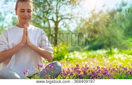 Beautiful woman doing yoga exercise outdoors, nice female in lotus pose meditate with closed eyes in beautiful blooming spring garden, healthy lifestyle, relaxation and wellness concept