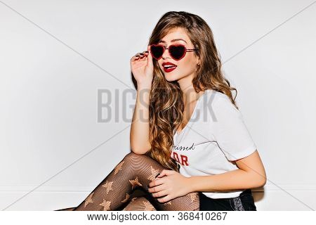 Fashionable Young Woman With Red Lips Holding Funny Sunglasses On White Background. Interested Beaut