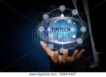 Fintech Concept. Man Demonstrating Different Icons On Dark Blue Background, Closeup
