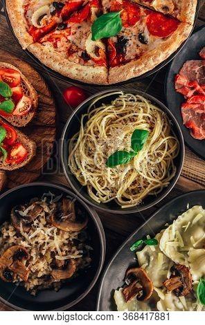 Table Of Italian Meals On Plates Pizza, Pasta, Ravioli, Carpaccio, Mushroom Risotto, Caprese Salad A