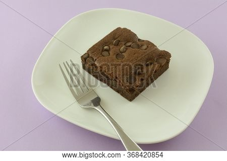 Chocolate Chip Brownie Square On White Dessert Plate With Fork On Lavender Background