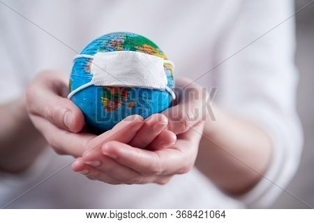 woman holding globe with protective mask