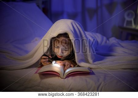 Child Asian Girl Reading A Book With Flashlight Under The Blanket On Bed In A Dark Bedroom At Night