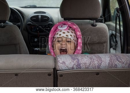 A Little Girl In Pink Clothes Screams In The Back Seat Of A Passenger Car. Portrait Of A Joyfully Sc