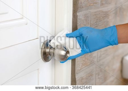 Coronavirus Covid-19 Prevention, Close Up Of Hand Cleaning Doorknob With Antibacterial Disinfecting