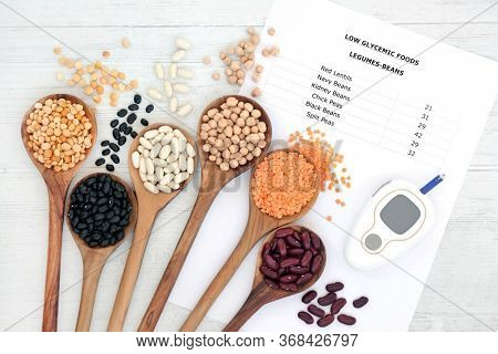 Low glycemic food list for diabetics with blood sugar testing monitor and legumes. Below 55 on the GI index and high in vitamins, minerals, anthocyanins, antioxidants & smart carbs. On rustic wood.