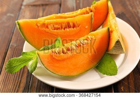 melon sliced with mint leaf on plate