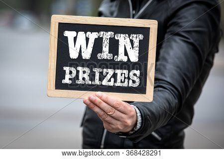 Win Prizes Concept. Text On Chalk Board. Woman In Jacket
