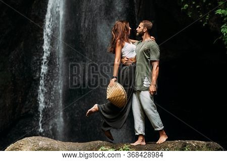 A Man Embraces A Woman At A Waterfall. A Couple In Love At A Waterfall. Honeymoon Trip. Happy Couple