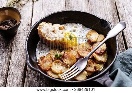 Fried Eggs And Potatoes In Cast Iron Skillet On Rustic Wooden Table. Skillet Breakfast. Selective Fo