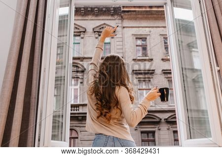 Indoor Portrait From Back Of Slim Girl With Long Curly Hair Wears Jeans. Stunning Young Female Model