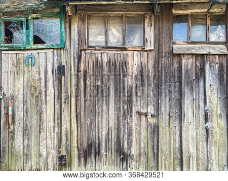 Old Weathered Wooden Barn Wall. Closed Doors With Padlocks And Windows With Broken Glass