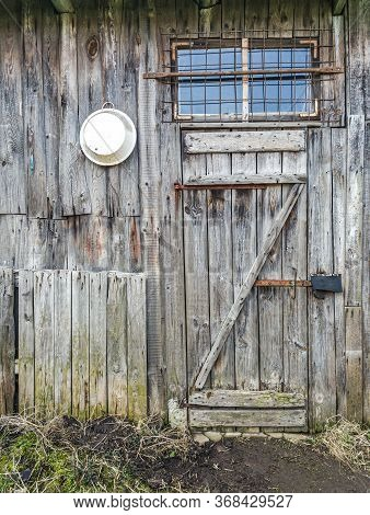 Old Weathered Wooden Shed Wall With Closed Door And Window