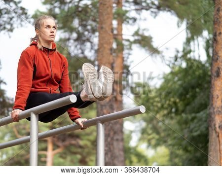 Beautiful Blond Caucasian Girl Doing Leg Raises On Parallel Bars In Sports Ground Outdoor In Summer,