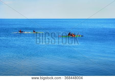 A Company Of Young People On Kayaks Is Training At Sea. Four Multi-colored Canoes Sail In The Blue S