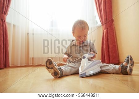 Young Parent Helper Little Baby Boy With Iron. Interested Cute Toddler Child Studying Electric Appli