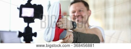 Man Raised His Leg And Shows Sneaker To Camera. Video Product Review Affects Potential Buyer. Descri