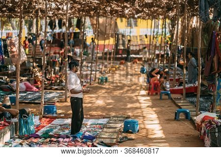 Anjuna, Goa, India - February 19, 2020: Man Seller Sells Indian Clothes In The Anjuna Market.