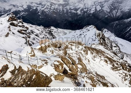 Snow Capped Mountains Range During Winter In Shilthorn, Switzerland, Walkway On Rock Hill Covered By
