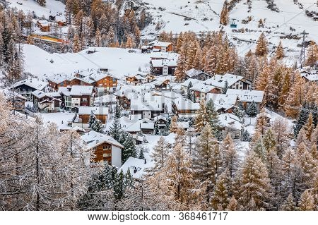 Aerial View Over Snow Capped Village On Hill Slope Inside Pine Woods Covered By Snow In Winter, Zerm