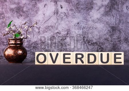 Word Overdue Made With Wood Building Blocks On A Gray Background