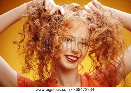 Happy laughing girl enjoys her beautiful red curly hair. Close-up portrait over yellow background. Hair care, hair coloring.