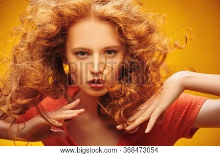 Long curly red hair. Portrait of a beautiful fashion girl with magnificent long hair in motion. Yellow background. Flying hair.