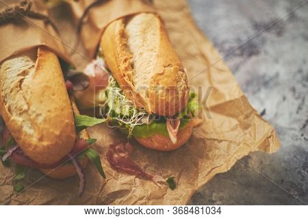 Tasty homemade sandwiches Baguettes bread with various healthy ingredients. Olives, tomatoes, ham, lettuce, garlic and spices over brown baking paper. Take away option. Breakfast take away concept