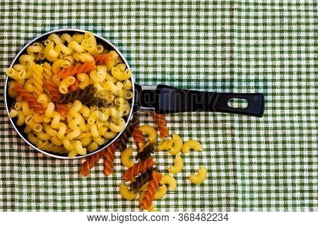 Small Mini Frying Pan With Tricolor Raw Fusilli Pasta In A Rustic Composition.