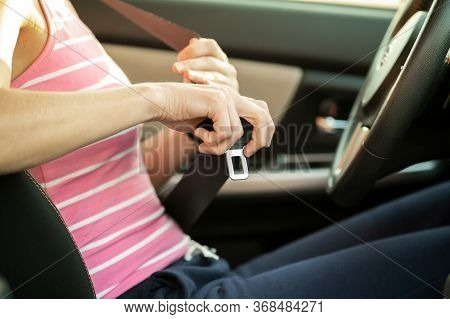 Close Up Of Woman Hand Fastening Seat Belt While Sitting Inside A Car For Safety Before Driving On T
