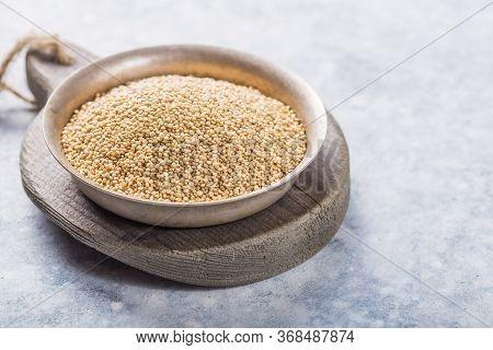 Raw  White  Quinoa Seeds (lat. Chenopodium Quinoa) On  Plate With Wooden Spoon. Raw  Quinoa Seeds