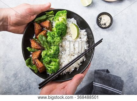 Vegan Teryaki  Tempeh Or Tempe Buddha Bowl  With Rice, Steamed Broccoli, Spinach  And Lime On Gray B