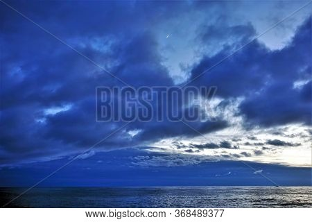 Beautiful Evening Cloudy Sky. Above The Calm Blue Sea, Blue Clouds. Between The Clouds Is A Small Yo