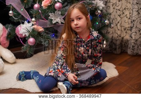 New Year's Concept. Adorable Cute Little Girl Near A Christmas Tree. New Year. Girl Near The New Yea