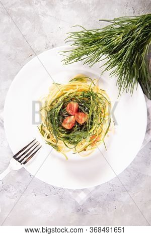 Spaghetti With Agretti, A Spring Vegetable From Italy, And And Ingredients On A White Plate On A Gra