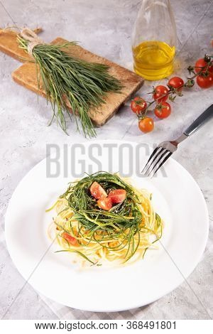 Spaghetti With Agretti, A Spring Vegetable From Italy, And And Ingredients And Fork On A White Plate
