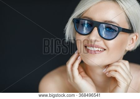 Stylish Blond Woman With Short Hair Cut In Trendy Sun Glasses With Black Background. Beauty Blond Gi