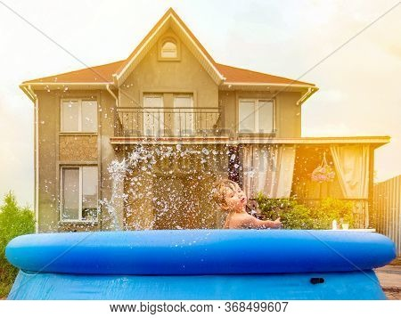 Pool On Backyard Of House. Kid Enjoying Summer Outdoor Of House. Boy Playing In The Pool. Child Enjo