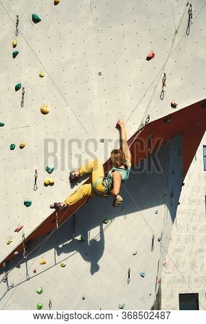 Strong Woman Climber Climbing On Tough Sport Route In Climbing Gym, Resting And Chalking Hands.