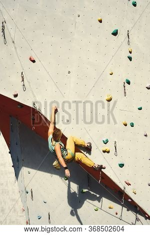 Woman Climber In Bright Yellow Pants Climbing On Artificial Rock Wall In Climbing Gym, Resting And R