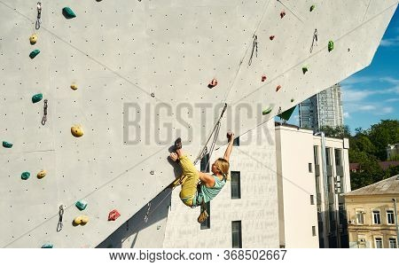 Sports Girl Climber Climbing On Artificial Rock Wall In Outside Climbing Gym. Strong Woman Making Ha