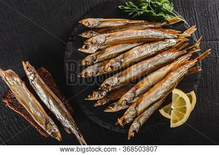 Smoked Fishes Sprat Marinated With Spices, Salt, Greens And Slice Of Bread On Plate Over Dark Stone